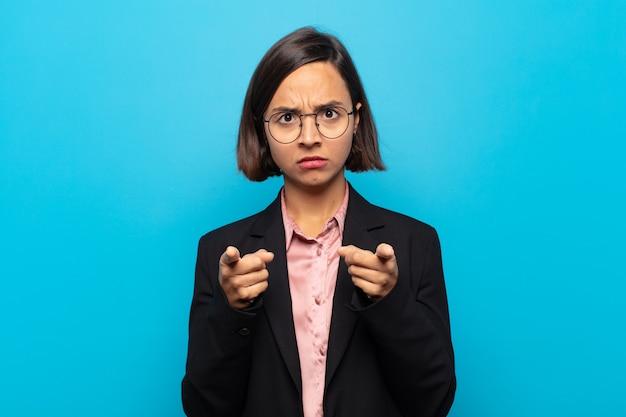 両指と怒りの表情で前を向いて、あなたに義務を果たすように言っている若いヒスパニック系女性