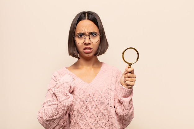 Young hispanic woman pointing to self with a confused and quizzical look, shocked and surprised to be chosen
