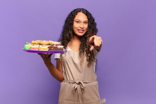 당신을 선택, 만족, 자신감, 친절한 미소로 가리키는 젊은 히스패닉 여자. 요리 케이크 개념