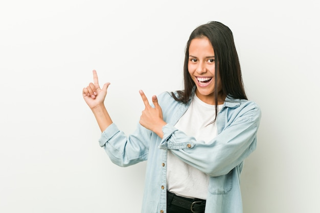 Young hispanic woman pointing with forefingers to a copy space, expressing excitement and desire.