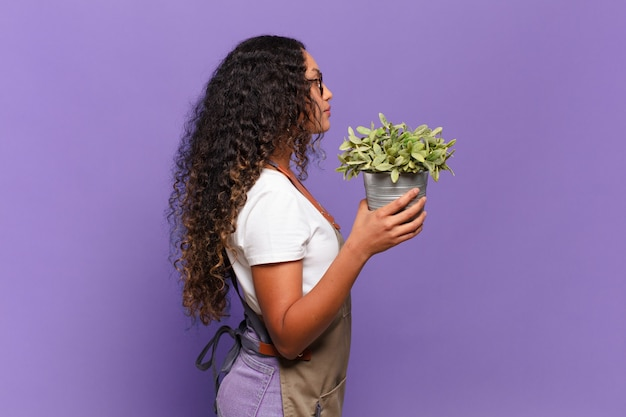 Young hispanic woman on profile view looking to copy space ahead, thinking, imagining or daydreaming. garden keeper concept