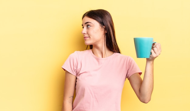 Young hispanic woman on profile view thinking, imagining or daydreaming. coffee cup concept