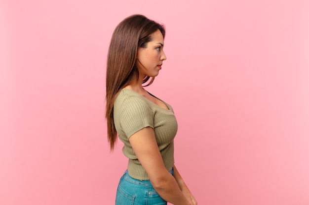 Young hispanic woman on profile view thinking, imagining or daydreaming