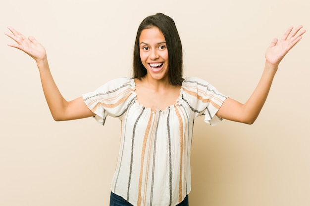 Young hispanic woman receiving a pleasant surprise, excited and raising hands.