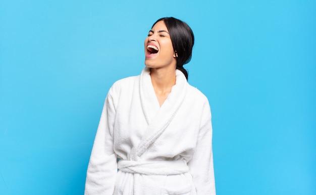 若いヒスパニック系の女性が猛烈に叫び、積極的に叫び、ストレスと怒りを感じています。バスローブのコンセプト