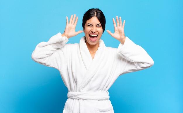頭の横に手を置いて、パニックや怒り、ショック、恐怖、激怒で叫んでいる若いヒスパニック系女性。バスローブのコンセプト