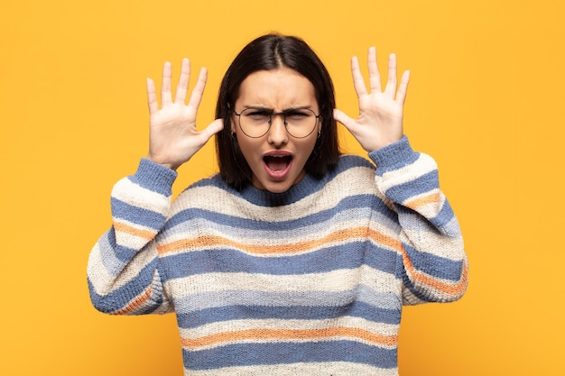 頭の横に手を置いて、パニックや怒り、ショック、恐怖、激怒で叫んでいる若いヒスパニック系女性