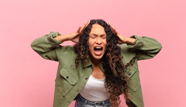 Молодая латиноамериканка кричит от паники или гнева, шокирована, напугана или разъярена, положив руки на голову