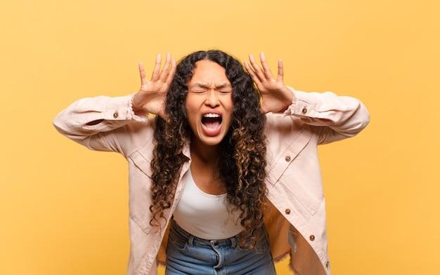 Молодая латиноамериканка, кричащая от паники или гнева, шокированная, испуганная или разъяренная, с руками у головы