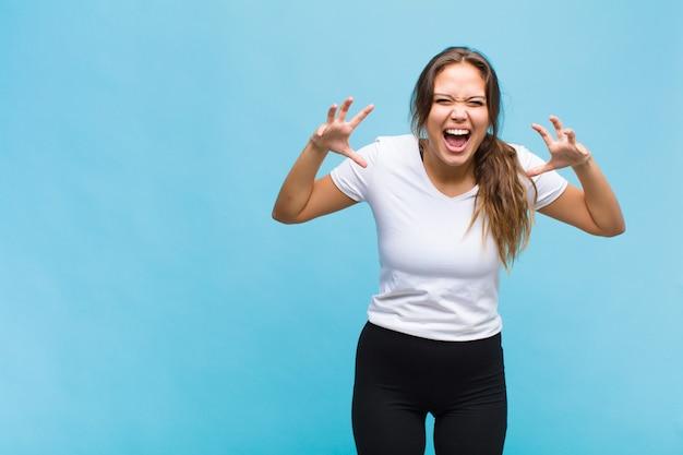 Молодая латиноамериканская женщина кричит от паники или гнева