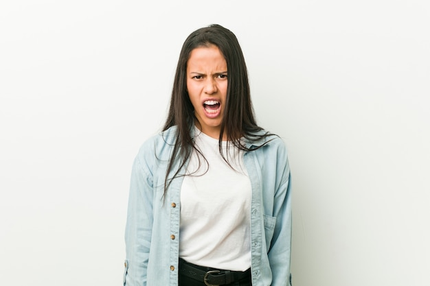 Young hispanic woman screaming very angry and aggressive.