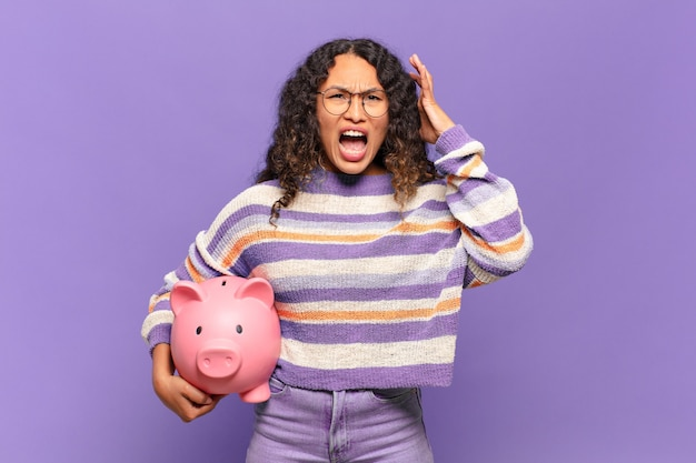 Young hispanic woman screaming with hands up in the air, feeling furious, frustrated, stressed and upset. piggy bank concept