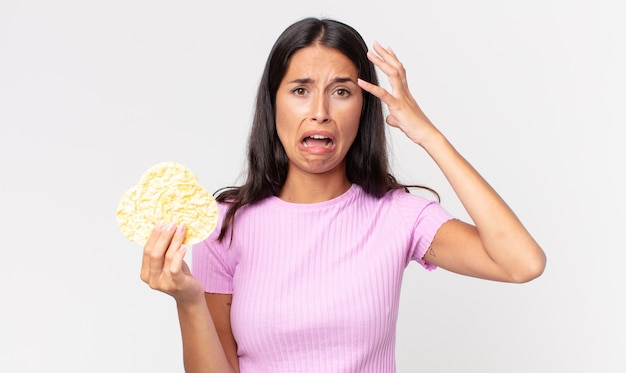 Young hispanic woman screaming with hands up in the air and holding a rice cookie. diet concept
