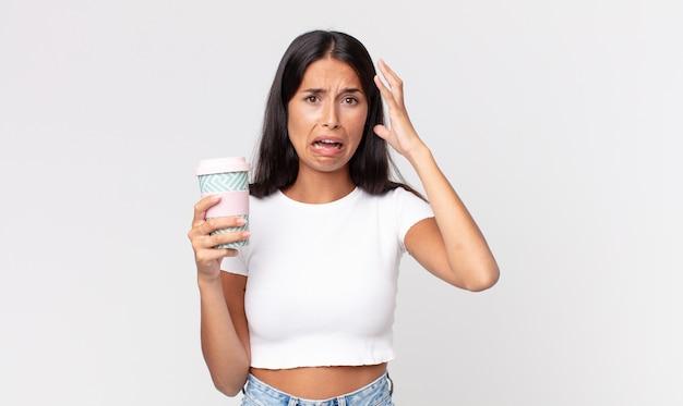 젊은 히스패닉계 여성이 손을 높이 들고 테이크아웃 커피 용기를 들고 소리를 지른다