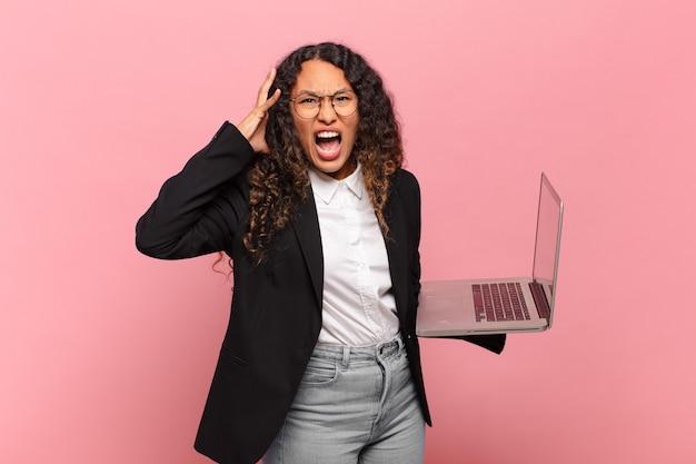 空中で手を上げて叫び、激怒し、欲求不満を感じ、ストレスを感じ、動揺している若いヒスパニック系女性。ノートパソコンのコンセプト