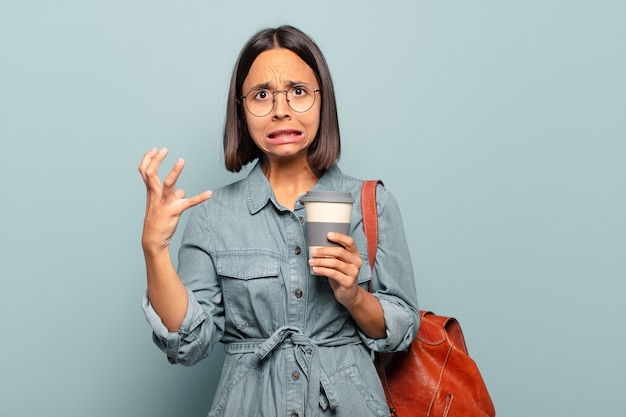Молодая латиноамериканская женщина кричит с поднятыми руками, чувствуя ярость, разочарование, стресс и расстройство