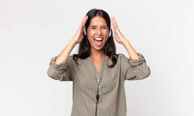 헤드셋을 들고 공중에 손을 들고 비명을 지르는 젊은 히스패닉계 여성. 텔레마케팅 개념