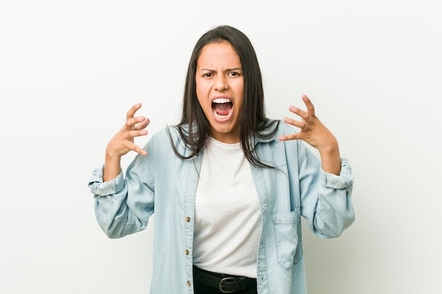 Young hispanic woman screaming with rage.