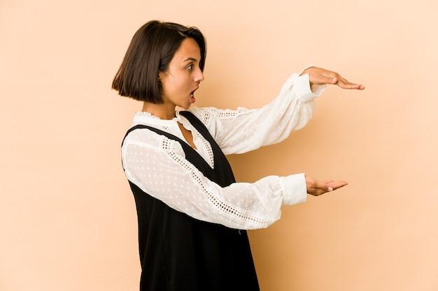 若いヒスパニック系の女性は、手の間にコピースペースを持ってショックを受けて驚いた。