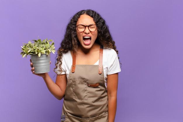 Молодая латиноамериканка агрессивно кричит, выглядит очень рассерженной, расстроенной, возмущенной или раздраженной, кричит «нет». концепция садовника