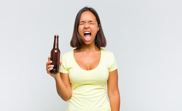 Молодая латиноамериканка агрессивно кричит, выглядит очень сердитой, расстроенной, возмущенной или раздраженной, кричит нет