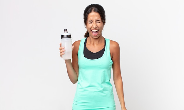 Young hispanic woman shouting aggressively, looking very angry and holding a water bottle. fitness concept