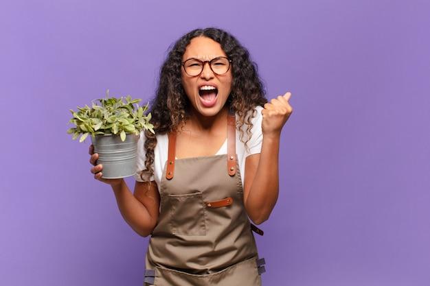 Молодая латиноамериканская женщина агрессивно кричит с сердитым выражением лица или со сжатыми кулаками, празднуя успех. концепция садовода
