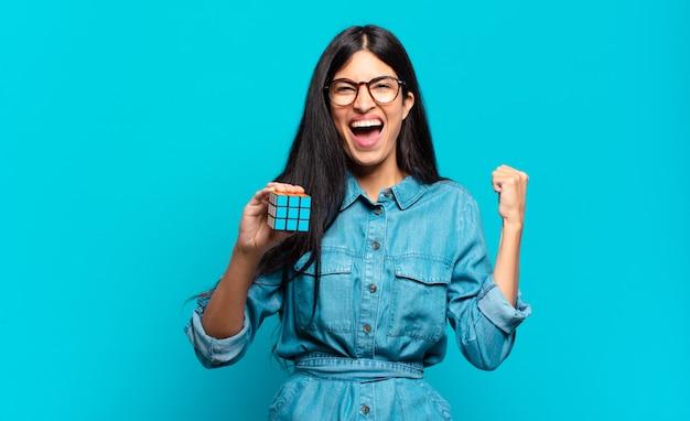 화가 난 표정으로 또는 주먹으로 공격적으로 외치는 젊은 히스패닉 여자는 성공을 축하합니다. 지능 문제 개념