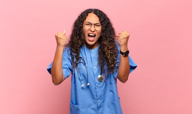 화가 난 표정으로 또는 주먹으로 공격적으로 외치는 젊은 히스패닉 여자는 성공을 축하합니다. 간호사 개념