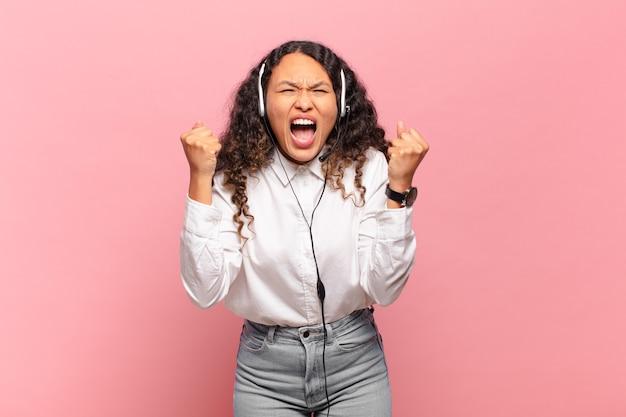 Молодая латиноамериканская женщина агрессивно кричит с сердитым выражением лица или со сжатыми кулаками, празднуя успех. концепция телемаркетинга