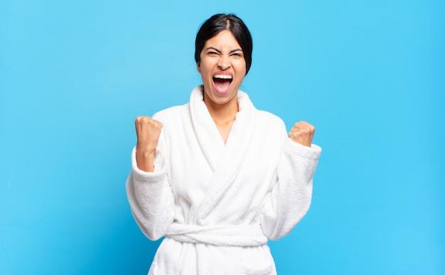 화가 난 표정으로 또는 주먹으로 공격적으로 외치는 젊은 히스패닉계 여성이 성공을 축하합니다.