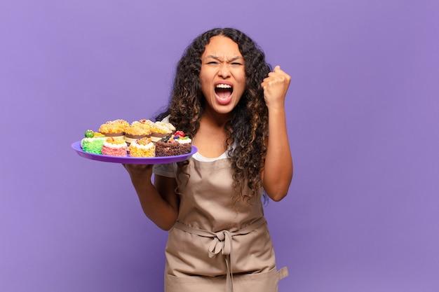 怒った表情で、または拳を握り締めて成功を祝って積極的に叫ぶヒスパニック系の若い女性