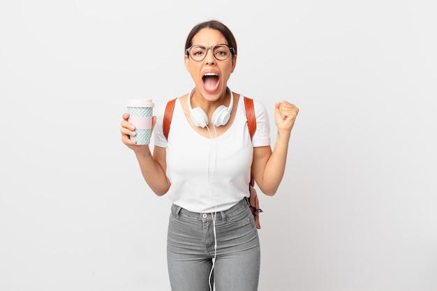Молодая латиноамериканская женщина кричит агрессивно с сердитым выражением лица. студенческая концепция
