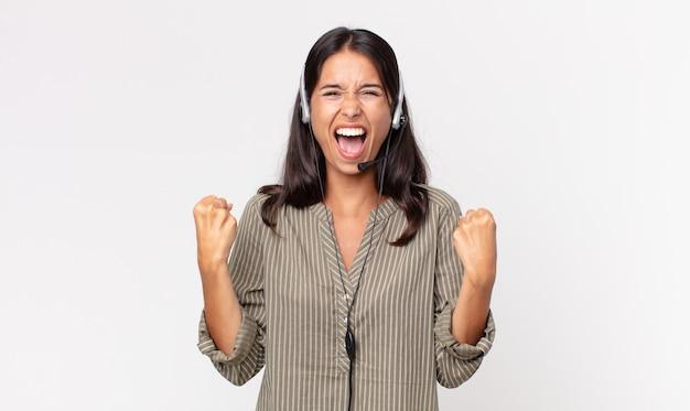 헤드셋으로 화난 표정으로 공격적으로 외치는 젊은 히스패닉계 여성. 텔레마케팅 개념