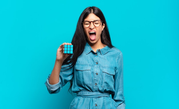 Young hispanic woman shouting aggressively with a rubik cube