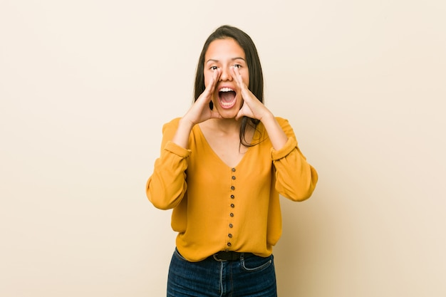 Young hispanic woman shouting excited to front.