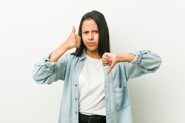Young hispanic woman showing thumbs up and thumbs down, difficult choose