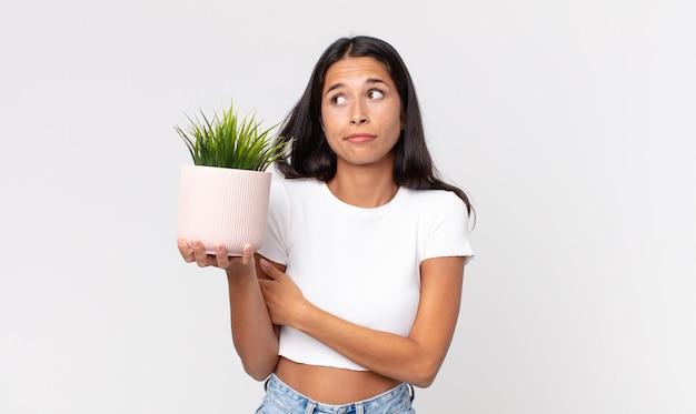 젊은 히스패닉 여성이 어깨를 으쓱하고 혼란스럽고 불확실하다고 느끼며 장식용 식물을 들고 있다