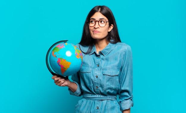 젊은 히스패닉 여성이 어깨를 으쓱하고 혼란스럽고 불확실하다고 느끼며 팔짱을 끼고 어리둥절한 표정으로 의심합니다. 지구 행성 개념