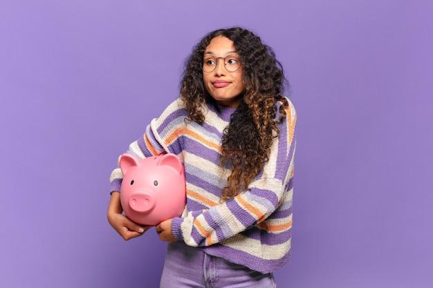 若いヒスパニック系女性は肩をすくめ、混乱し、不安を感じ、腕を組んで困惑した表情で疑っています。貯金箱のコンセプト