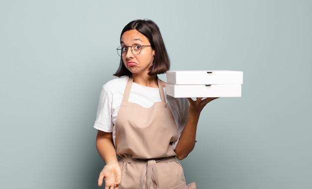 肩をすくめる若いヒスパニック系女性、混乱して不安を感じ、腕を組んで困惑した表情で疑う