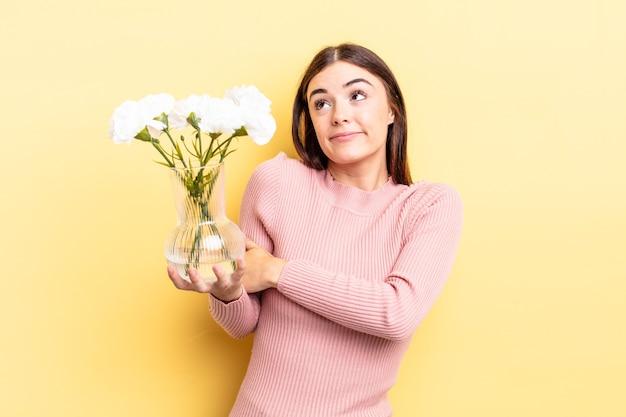 若いヒスパニック系女性は肩をすくめ、混乱し、不安を感じています。植木鉢のコンセプト