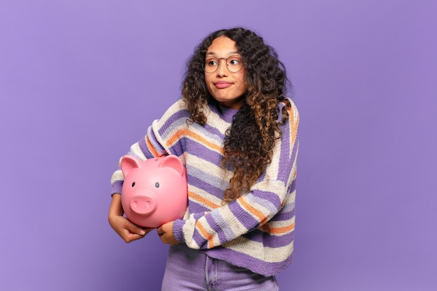 Young hispanic woman shrugging, feeling confused and uncertain, doubting with arms crossed and puzzled look. piggy bank concept