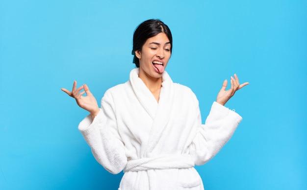 멍청하고, 미친, 혼란스럽고, 당황한 표정으로 어깨를 으쓱하는 젊은 히스패닉 여성 목욕 가운 개념