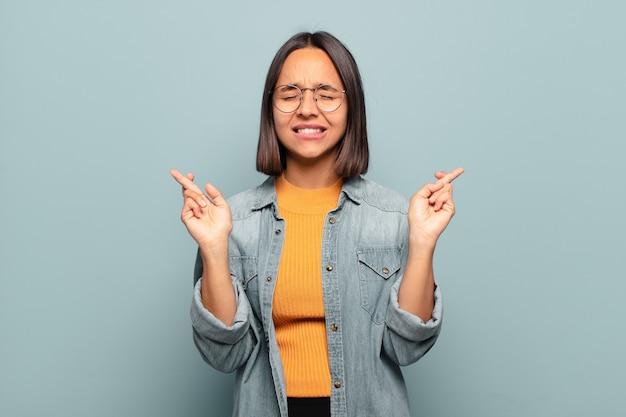 젊은 히스패닉계 여성은 웃고 걱정스럽게 두 손가락을 교차하며 걱정하고 행운을 빌거나 바라고 있습니다.