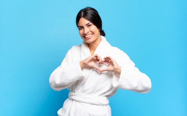 若いヒスパニック系の女性が笑顔で幸せ、かわいい、ロマンチックで恋をして、両手でハートの形を作っています。バスローブのコンセプト