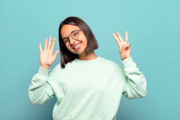 若いヒスパニック系の女性が笑顔でフレンドリーに見え、手を前に向けて8番または8番を示し、カウントダウン