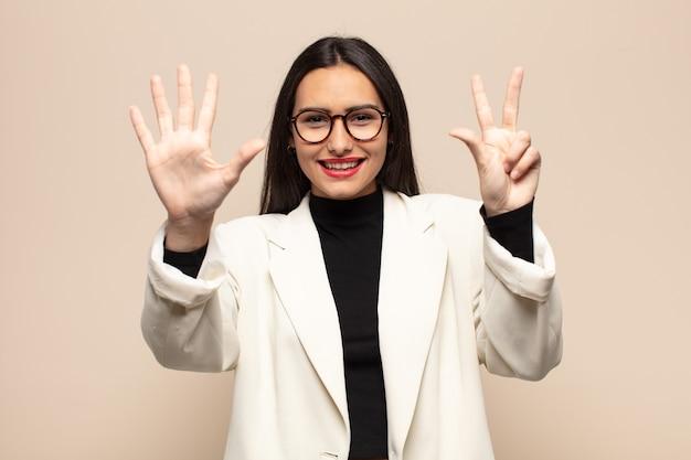 Молодая латиноамериканская женщина улыбается и выглядит дружелюбно, показывает номер восемь или восьмой рукой вперед и ведет обратный отсчет