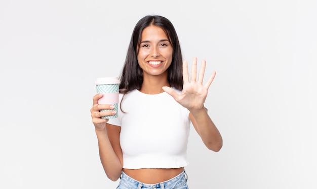Молодая латиноамериканка улыбается и выглядит дружелюбно, показывает номер пять и держит контейнер для кофе на вынос
