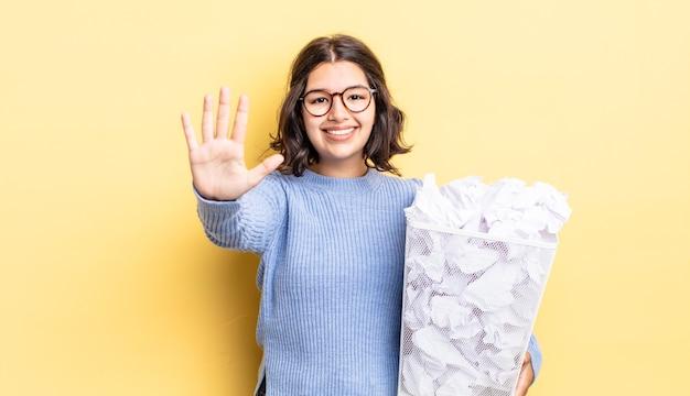 Молодая латиноамериканская женщина улыбается и выглядит дружелюбно, показывая концепцию мусора номер пять